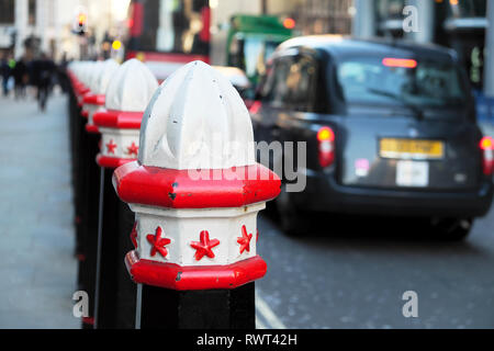 A row of Corporation of London traffic bollards and taxis on Cannon Street in the City of London England UK  KATHY DEWITT - Stock Image