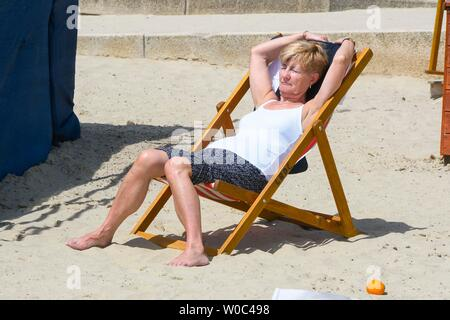 Lyme Regis, Dorset, UK.  27th June 2019. UK Weather.  A woman sunbathing at the seaside resort of Lyme Regis in Dorset as they enjoy a day of clear blue skies and scorching sunshine.   Picture Credit: Graham Hunt/Alamy Live News - Stock Image