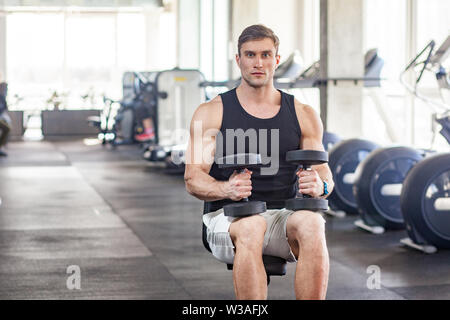 Portrait of young adult muscular built handsome athlete working out in a gym, sitting on a weightlifting machine and holding two dumbbell on the knees - Stock Image