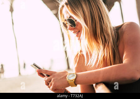 Happy young people using mobile phone. Beautiful woman, caucasian sitting outdoor in a bench - Stock Image