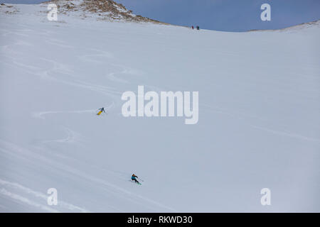 Skiers riding off piste in fresh powder after hiking to the summit of La Capa. - Stock Image