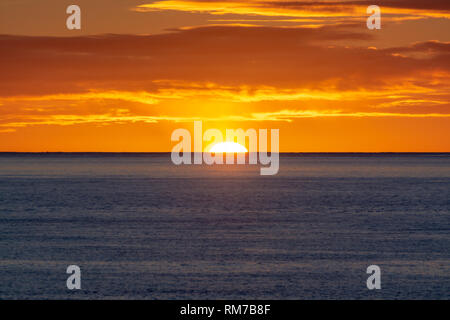 Landscape with  colorful sunrise over dark blue ocean water - Stock Image