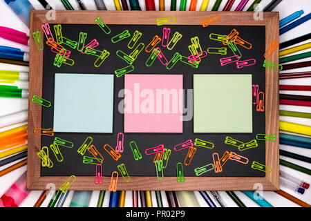 Colorful sticky notes on chalkboard with pencils on background, blank copy space - Stock Image