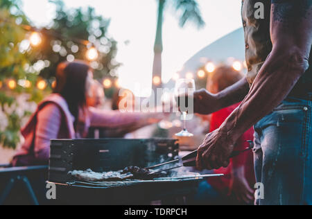 Happy family doing barbecue dinner on rooftop at night - Close up hand of tattoo man cooking at bbq grill outdoor - Stock Image