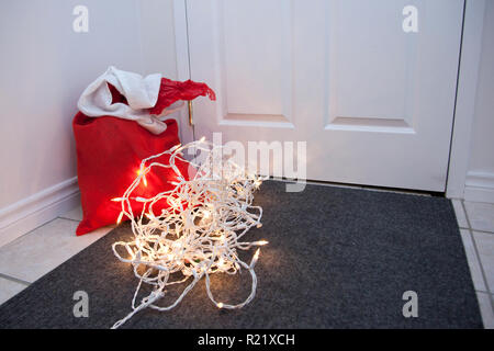A red bag with presents and a tangle of christmas lights by the door of a house - Stock Image