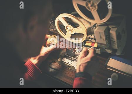 man repairing broken 8mm video tape with glue - Stock Image