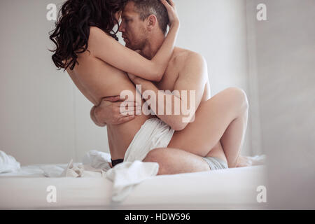 Young couple having sex in bedroom. Sensual lovers making love in bed. - Stock Image
