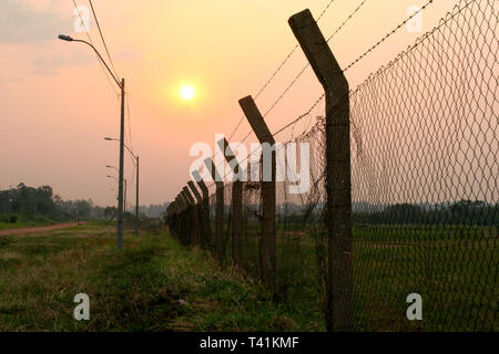 Perimeter fence, chain-link fencing showing the diamond patterning, with barbed wire protecting a property - Stock Image