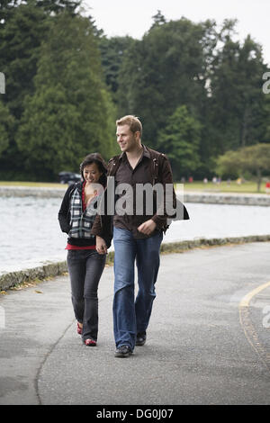 A young couple walking along the seawall at Stanley Park, Vancouver, British Columbia, Canada - Stock Image
