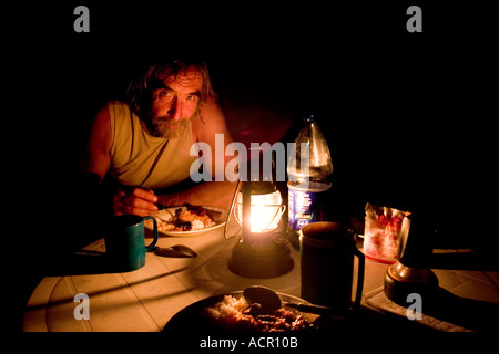 Tourist enjoying evening meal at the hippo sanctuary Wechiau Northwestern Ghana prepared by the guide on cokepot - Stock Image