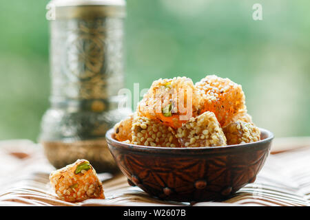 Traditional Turkish delight. lokum. Oriental sweets with sesame and pistachios in a ceramic bowl on the table. A treat for tea. Selective focus, copy - Stock Image