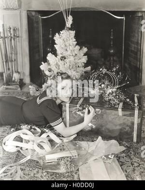 Woman lying on floor by Christmas gift and tree at home - Stock Image