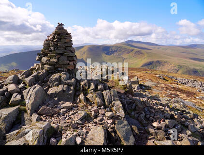 The summit cairn (pile of stones) of Carrock Fell with Bowscale Fell and Blencathra in the distance in the English - Stock Image