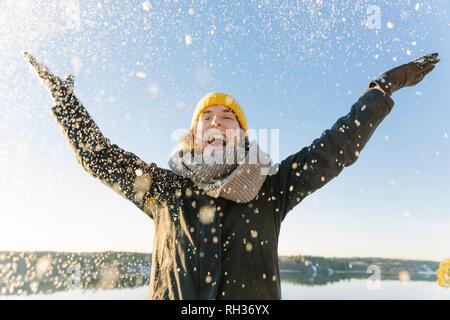 Woman throwing snow - Stock Image