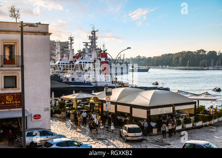 An Italian family waits outside a waterfront restaurant near naval ships and boats on the promenade of the port city of Brindisi, Italy - Stock Image