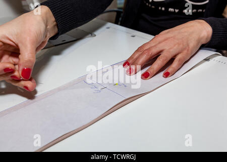 Female tailor hands with cloth, pattern and needle in the workshop - Stock Image