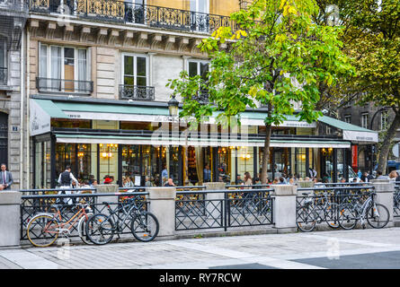 Bikes are parked in front of the Brasserie Les Deux Palais, a notable sidewalk cafe and Parisian restaurant on the Ile de la Cite in Paris France - Stock Image