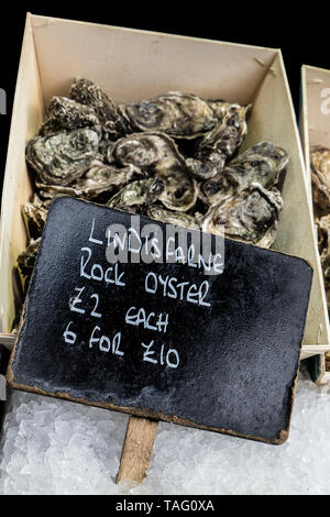 Pacific Rock Oysters (Crassostrea Gigas) from Lindisfarne at Borough Market Fishmongers stall. Grown on the seashore within the Lindisfarne National Nature Reserve at the site of the Oyster beds established by the Monks of Lindisfarne Priory. Northumberland UK - Stock Image