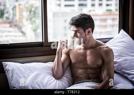 Naked young man with muscular body on bed with mug or cup in hand with coffee or tea - Stock Image