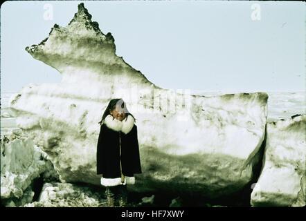 Eskimo child in front of ice block; Point Barrow, Alaska. - Stock Image