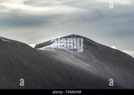Light streams over a snow topped mountain off the coast of Trondheim, Norway - Stock Image