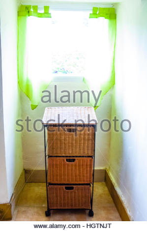 Stacked laundry baskets on wheels in a French Home in Mantilly, Orne, France, Europe - Stock Image