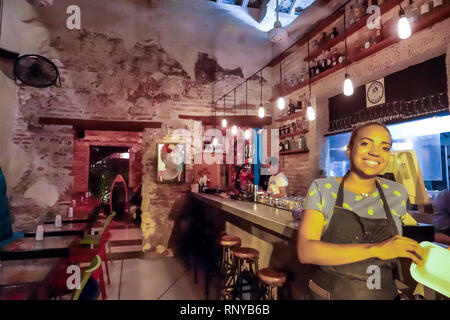 Cartagena Colombia Old Walled City Center centre Getsemani restaurant bar inside Hispanic woman waitress employee - Stock Image