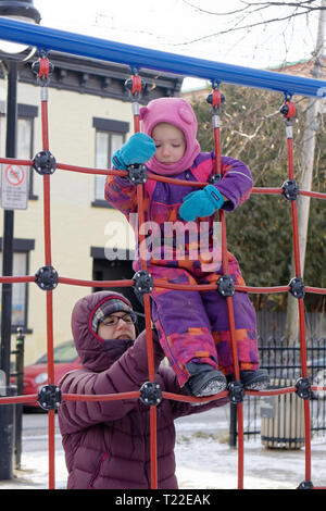 A mother helps her little girl (4 yrs old) on a climbing frame in Quebec in winter - Stock Image