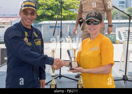 180903-N-GX781-0110 CARTAGENA, Colombia (Sept. 3, 2018) Cmdr. Fiona Halbritter, commanding officer of the Whidbey Island-Class Dock Landing Ship USS Gunston Hall (LSD 44), right, receives a trophy on behalf of the Sailors aboard the ship following a tug of war competition between partner nations during UNITAS 2018. UNITAS is an annual international exercise in the U.S. Southern Command area of responsibility where partner nations participate in multinational exchanges to enhance interoperability, increase regional stability, and build and maintain regional relationships with countries througho - Stock Image