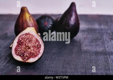 Figs isolated on dark wood background - Stock Image
