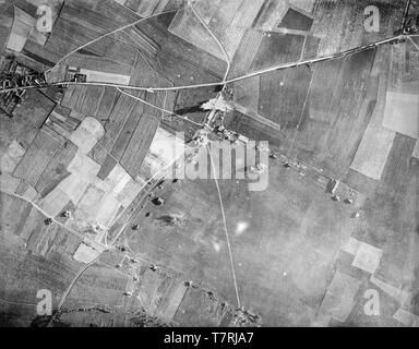 A contemporary British black and white photograph taken in 1917 from an aeroplane during the First World War. Photograph shows the bombing of a target in Northern France. A British aeroplane can be seen in small detail flying just over the road that runs left to right, having just dropped its bombs.  Aerial bombing World war One. - Stock Image