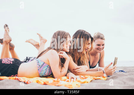 Summer concept tourists with three friends girls lay down on the beach for a sunbath together taking selfie picture with smart phone - cheerful happy  - Stock Image