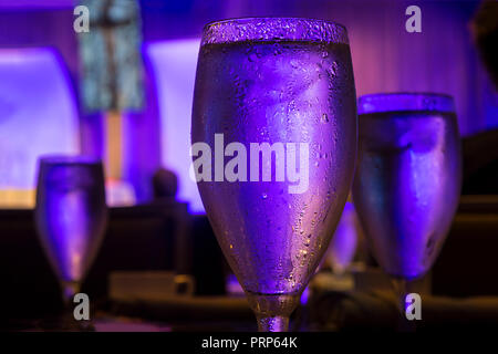 Water Glass Sweating With Blue Light In Restaurant - Stock Image