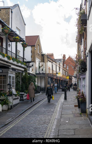 People strolling through Perrin's Court, a pretty narrow street of shops, cafes, and restaurants in Hampstead, London, England, UK - Stock Image