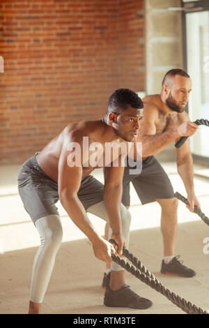 Two multiethnic atletic friends test the strength of an invisible enemy with battle rope in crossfit style gym, standing with legs apart, shoulder-wid - Stock Image