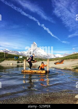 Two childs crossing Leisee lake, Sunegga, Rothorn Paradise: one of top five lakes destination around Natterhorn Peak in Zermatt, Switzerland, Europe - Stock Image