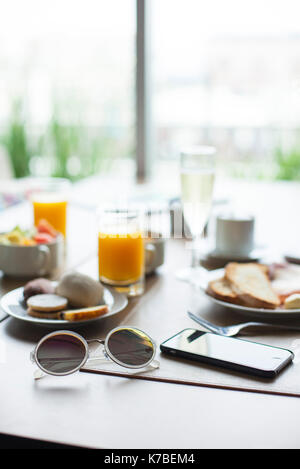 Sunglasses and smartphone on breakfast table in cafe - Stock Image