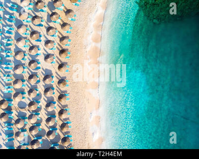 Aerial view of a empty beach with sun beds and umbrellas in Greece - Stock Image