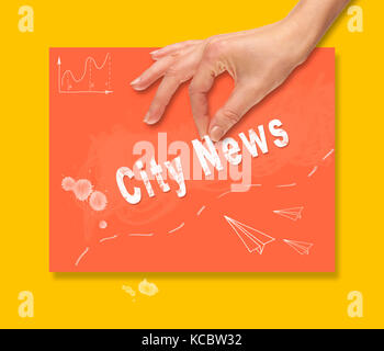 A hand picking up a City News concept on a colorful drawing board. - Stock Image