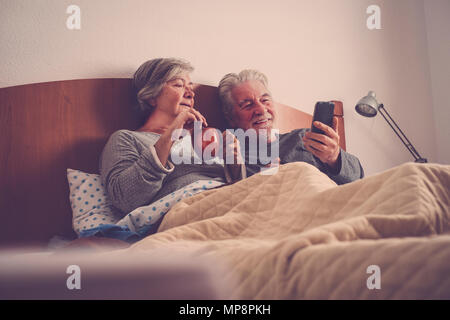 Couple of senior people married rest in bed, enjoying the breakfast and a cup of tea or coffee. Happy retired caucasian man and woman - Stock Image