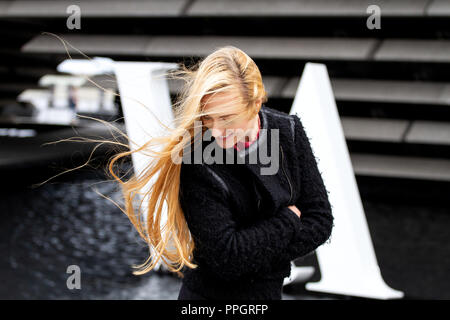 Dundee, Tayside, Scotland, UK. 25th September, 2018. UK weather: Strong winds with light rain sweeping across Tayside. A young blonde woman Rhianna Martin pays her first visit to the stunning new V&A building on a very windy day in Dundee, UK. Credits: Dundee Photographics / Alamy Live News - Stock Image