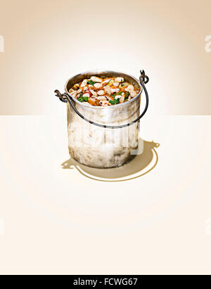 A bucket of swill on a beige background - Stock Image