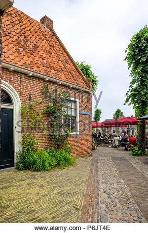 People lunch under umbrellas in outdoor cafe Vesting Bourtange, the star-shaped fortress in Groningen Province, The Netherlands. - Stock Image