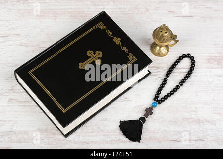 Holy Bible, rosary beads with cross and incense burner on white wooden background. Religion concept and faith. - Stock Image