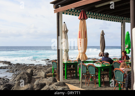 People dining in a beach restaurant with a view overlooking the sea in El Golfo, Lanzarote, Canary Islands, Spain - Stock Image