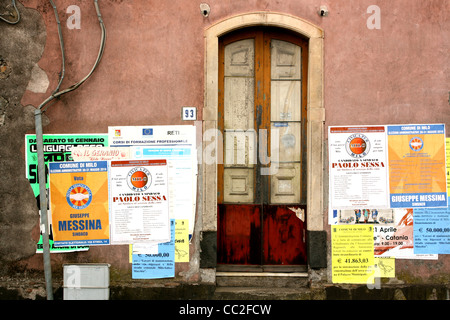 A small door with the number 93 next to it against a red wall in Sicily, Italy. Posters for local festivals decorate - Stock Image