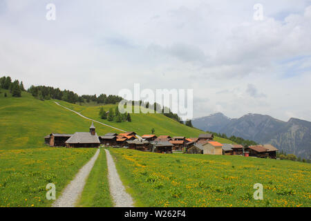 Swiss village situated high up on a hill top. Early summer. - Stock Image