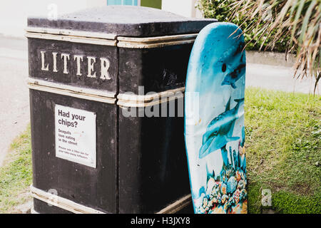 An abandoned body board propped up against a litter bin at Falmouth beach. - Stock Image