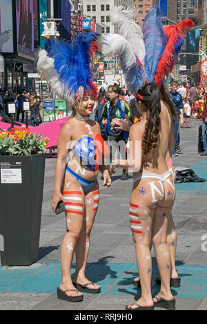 Three mostly naked desnudas have a chat in Times Square where they hustle tourists to get their photos taken with them - Stock Image