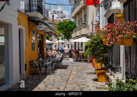 Estepona, Malaga, Spain: A colourful street scene: tourists browse the local restaurants - Stock Image